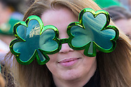 A woman with clover leaf glasses smiles for the camera during the St Patrick's Day Parade in Westminster, London.<br /> Picture by Paul Davey/Focus Images Ltd +447966 016296<br /> 13/03/2016