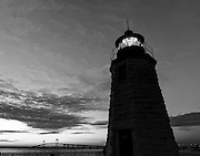 Newport Harbor Lighthouse known locally as the Goat Island Light House during the blue hour just after sunset with the Claiborne Pell Newport Bridge in the background, Newport, Rhode Island, USA in black and white. The octagonal granite lighthouse, painted white with a green beacon, was activated in 1842, replacing an earlier light. The lighthouse was automated in 1963, renovated in 1986, and in 2005 the current fixed green light was added. It is still an active aid to navigation. <br /> <br /> Coordinates: 41 29 36 N&nbsp;&nbsp; 71 19 37 W<br /> <br /> This image is also available in my portfolio in color.