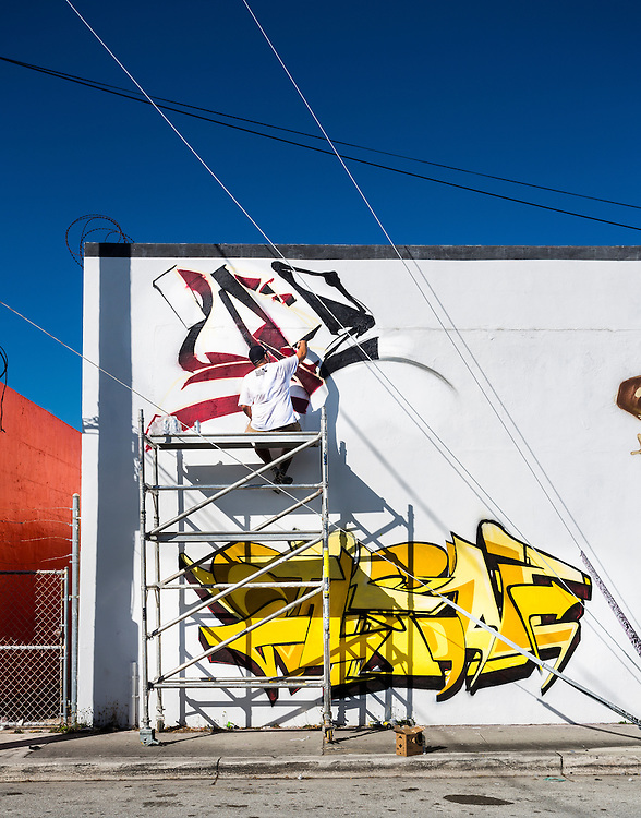 Artist on scaffold paints mural on a sunny day in Miami's Wynwood arts district.