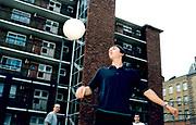 Three young men playing football.