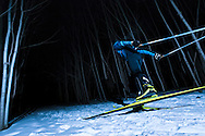 Cross-country skier at night in the woods.