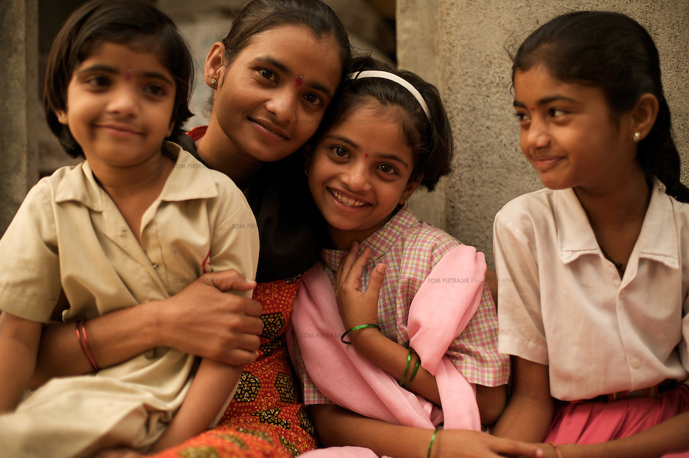 At home Vasanti and daughters Shrudha, 10 (HIV positive, in pink), Shubhada, 11 (HIV negative, right) and Vrinda, 8 (status not known). Vasanti Shinde, 26, works for the Save Foundation. Others neighbours<br /> <br /> Like many of the women who work for and with UNDP partners the Save Foundation, Vasanti Shinde, age 26, only found out that she was HIV positive after her husband became seriously ill with an AIDS-related illness five years ago. Vasanti's husband subsequently died. Vasanti now lives with her two younger daughters Shrudha, age 10, and Vrinda, 8, in the one-room home of her brother in Sangli city. Vasanti's elder daughter, eleven year old Shubhada is being brought up by her paternal grandmother and sees her mother during holidays. Vasanti knows that Shubhada is HIV negative and Shruda is positive but anxiety over the result means that she refuses to have Vrinda tested for HIV. For a monthly income of Rs.3500, Vasanti works as a field officer and counselor for the Save Foundation. She works in the positive-people's pharmacy for no pay. Her work with the Save Foundation entitles her access to a credit union which provides low interest loans covering medical expenses. Though first-line drugs and homeopathic medicine keep Vasanti healthy, she is prone to infection and recently suffered a bout of influenza. Vasanti is completely open about her HIV status and most of her neighbours know that she is HIV positive. Vasanti says that &quot;I used to feel like I was going to die. Now, because of the Save Foundation, I feel like I'm going to live.&quot; <br /> <br /> Photo: Tom Pietrasik<br /> Sangli, Maharashtra. India<br /> August 2008