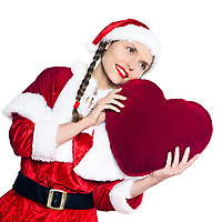 one woman dressed as santa claus holding big heart pillow on studio isolated white background