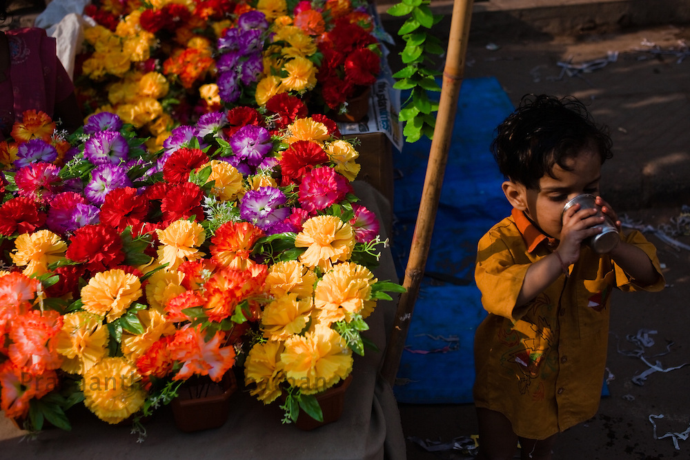 A boy drinks water next to his mothers flower stall during the Diwali sale season in Old Delhi area of New Delhi, India, November 3, 2010. Photographer: Prashanth Vishwanathan