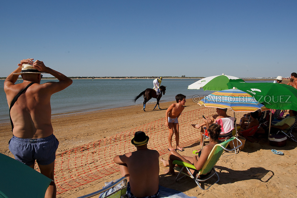12/08/2016. A jockey races his horse along the beach during the beach horse races on August 12, 2016 in Sanlucar de Barrameda, Cadiz province, Spain. Sanlucar de Barrameda yearly horse races traditional origin started with informal races of horse's owners delivering fish from the port to the markets. But the first formal races date back to 1845 and they are the second oldest in Spain, after Madrid. The horse races take place near the Guadalquivir river mouth during August