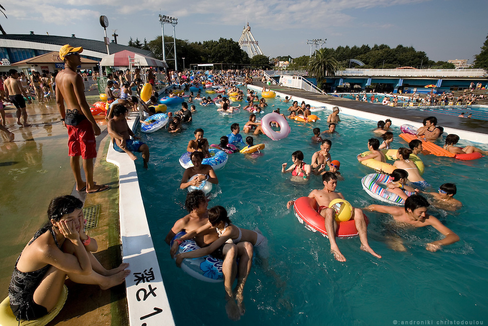 People escaping from the summer heat in the river-like swimming pool of TOSHIMAEN water park. The water moves around in the circle river, taking with it people floating in life-belts or people walking in it following the flow. Tokyo