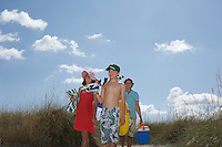 Parents with son (10-12) carrying beach accessories