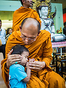 24 AUGUST 2015 - BANGKOK, THAILAND: A Buddhist monk comforts and prays with a boy at a memorial service for victims of the Erawan Shrine bombing. One week after the a bomb at the Erawan Shrine in the center of Bangkok killed dozens and hospitalized scores of people, police have not made any arrests. Police bomb sniffing dogs have been deployed to malls and markets around Bangkok. There was a large memorial service sponsored by businesses close the bomb site Monday evening.     PHOTO BY JACK KURTZ