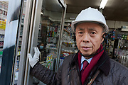 A man wears a helmet to protect him during aftershocks in a shop in Okubo after a magnitude .9 earthquake hit the Tohoku region of north east Japan causing tremors in Tokyo that stopped the train and cellphone networks. Many people were stranded in the centre of Tokyo over night. Tokyo, Japan Friday March 11th 2011