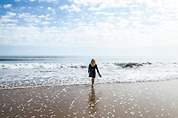 A woman wading in the surf on Ocean City beach holding her sandals in he hand, Ocean City, Maryland, USA.