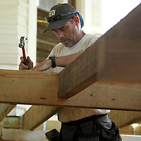 Ronnie Schutkesting, Facilities Director at the Private John Allen Fish Hatchery, secures new beams to help hold new composite decking that will be installed for the porch floor at the Fish Hatchery home Wednesday in Tupelo.