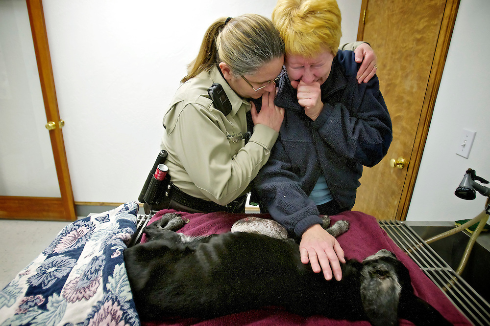 Karen Williams, a Kootenai County Sheriff animal control officer, comforts Jean Curran who cries over the dog she found Tuesday in the  Riverside Harbor subdivision in Post Falls. Curran took the dog to Hayden Pet Medical Center where it had to be euthanized due to its condition which is thought to be caused by abuse and neglect. The dog had a large tumor on its abdomen that dragged the ground when it walked, overgrown nails, was severely malnourished and major dental problems.