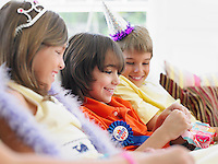Three children (7-12) sitting on sofa watching one open birthday present