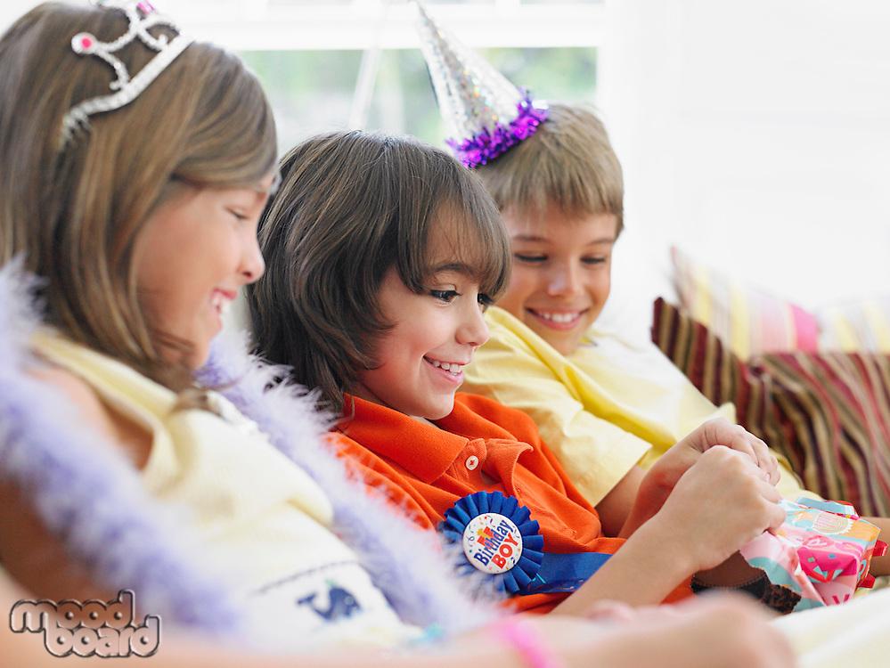 Three children (7-12) sitting on sofa watching one open birthday present