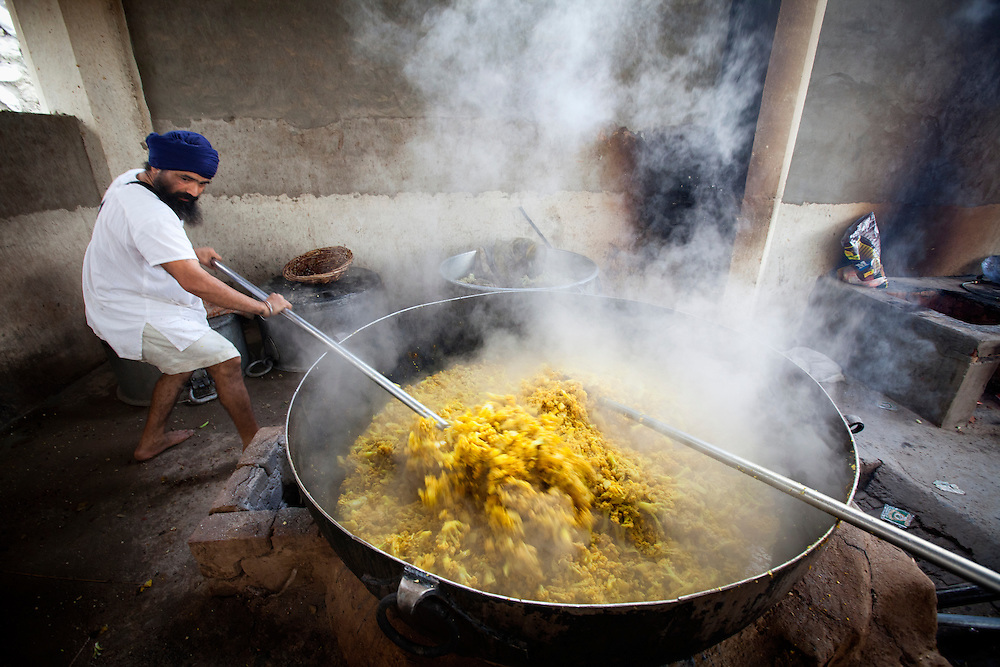 A cook in a Sikh kitchen cooking curry in an extremely large pot.<br />