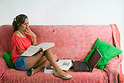 A teen studies on a couch in her room
