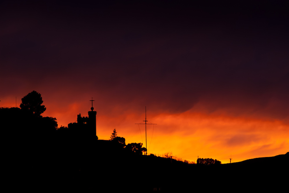 Lyttelton Timeball and signalling mast, silhouted against glowing sunrise surrounded by dramatic low cloud
