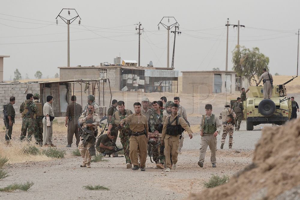 © Licensed to London News Pictures. 30/09/2015. Kirkuk, Iraq. Kurdish peshmerga evacuate a wounded colleague, who later died of his wounds, after he and three other fighters triggered an IED in the village of Mansoria near Kirkuk, Iraq.<br /> <br /> Supported by large amounts of coalition airstrikes, members of the Iraqi-Kurdish peshmerga today (30/09/2015) took part in an offensive to take seven villages across a large front near Kirkuk, Iraq. By mid afternoon the Kurds had reached most of their objectives, but suffered around 10 casualties all to improvised explosive devices. All seven villages were originally Kurdish and settled with other ethnic groups during the Iraqi Arabisation process of the 1970's and 80's. Photo credit: Matt Cetti-Roberts/LNP