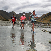 Runners Phil Gerard, Julie Brown and Colleen Thompson (right)    cross  Moke Creek on the Ben Lomond High Country Station during the Pure South Shotover Moonlight Mountain Marathon and trail runs. Moke Lake, Queenstown, New Zealand. 4th February 2012. Photo Tim Clayton