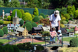© Licensed to London News Pictures. 29/08/2013. Beaconsfield, UK Children look at the village. People enjoy the sunshine and hot weather at Bekonscot Model Village in Berkshire today 29th August 2013. Bekonscot Model Village and Railway is the world's oldest and original model village, opening for the first time in 1929. With over 80 years of history, huge model railway, 1.5 acres of well kept gardens and finely detailed model buildings. Photo credit : Stephen Simpson/LNP