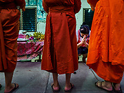 13 JANUARY 2019 - NAKHON PATHOM, THAILAND:  A woman prays after giving alms to female monks from Wat Songdhammakalyani. The Sangha Supreme Council, Thailand's governing body of Buddhist monks, bans the ordination of female monks, but hundreds of Thai women have gone abroad, mostly to Sri Lanka and India, to be ordained. There are about 270 women monks in Thailand and about 250,000 male monks. There are 7 monks and 6 novices at Wat Songdhammakalyani in Nakhon Pathom. It was the first temple in Thailand to have female monks. The temple opened 60 years ago and has always been a temple of women monks. Women can be ordained as novices in Thailand, but to be ordained as a full monk would require the participation of 10 female monks and 10 male monks, and male monks in Thailand are barred from participating in women's ordination ceremonies.     PHOTO BY JACK KURTZ