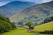 Car motoring along winding road through picturesque valley at Llanfihangel, Snowdonia, Gwynedd, Wales