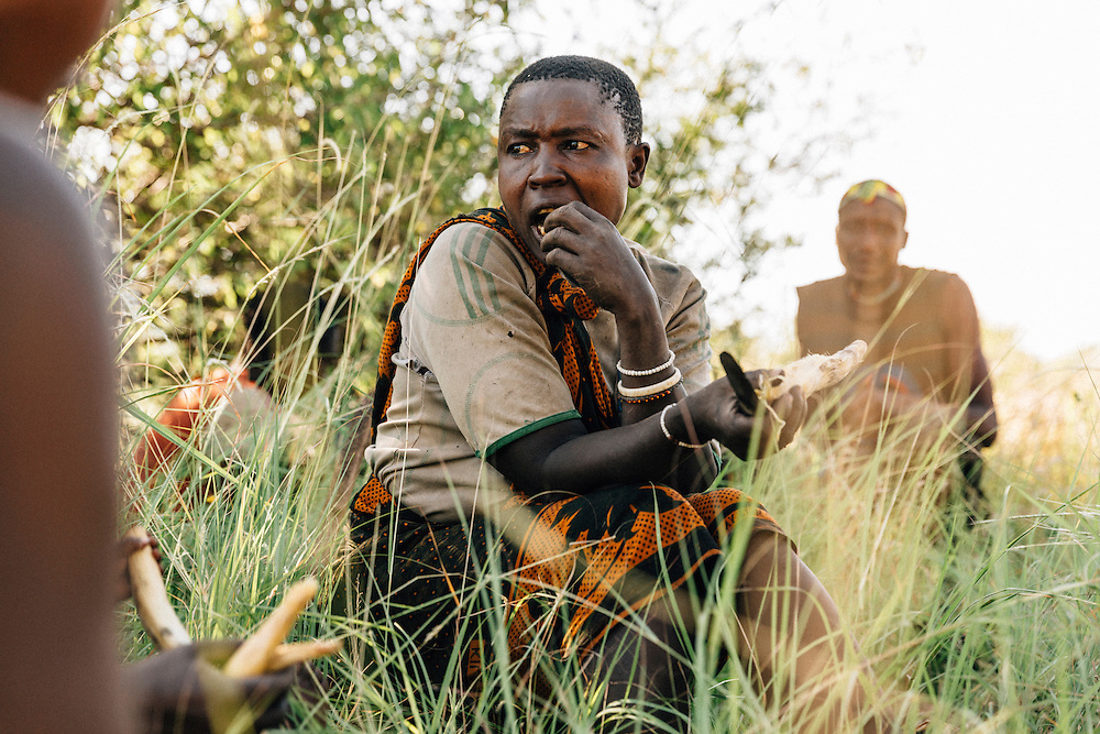 Members of the Hadza tribe stop in the shade for a smoke and to eat roasted tubers. Yaeda Valley, Northern Tanzania. Photo by Greg Funnell, March 2016.