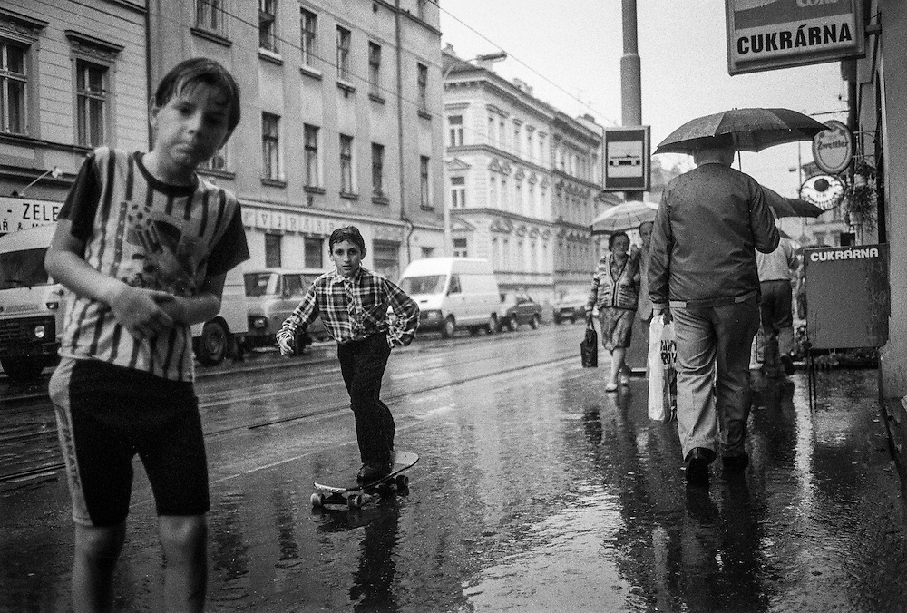 Boy with a skateboard riding Konevova street during a rainy day.