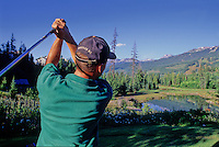 A male golfer tees off the 16th hole at the Whistler Golf Course in Whistler, BC Canada.