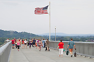 Highland, New York - People walk along the Walkway over the Hudson on May 27, 2012. Walkway Over the Hudson State Historic Park is a linear walkway spanning the Hudson River. At 212 feet tall and 1.28 miles long, it is the longest, elevated pedestrian bridge in the world. The walkway was formerly an abandoned railroad bridge.