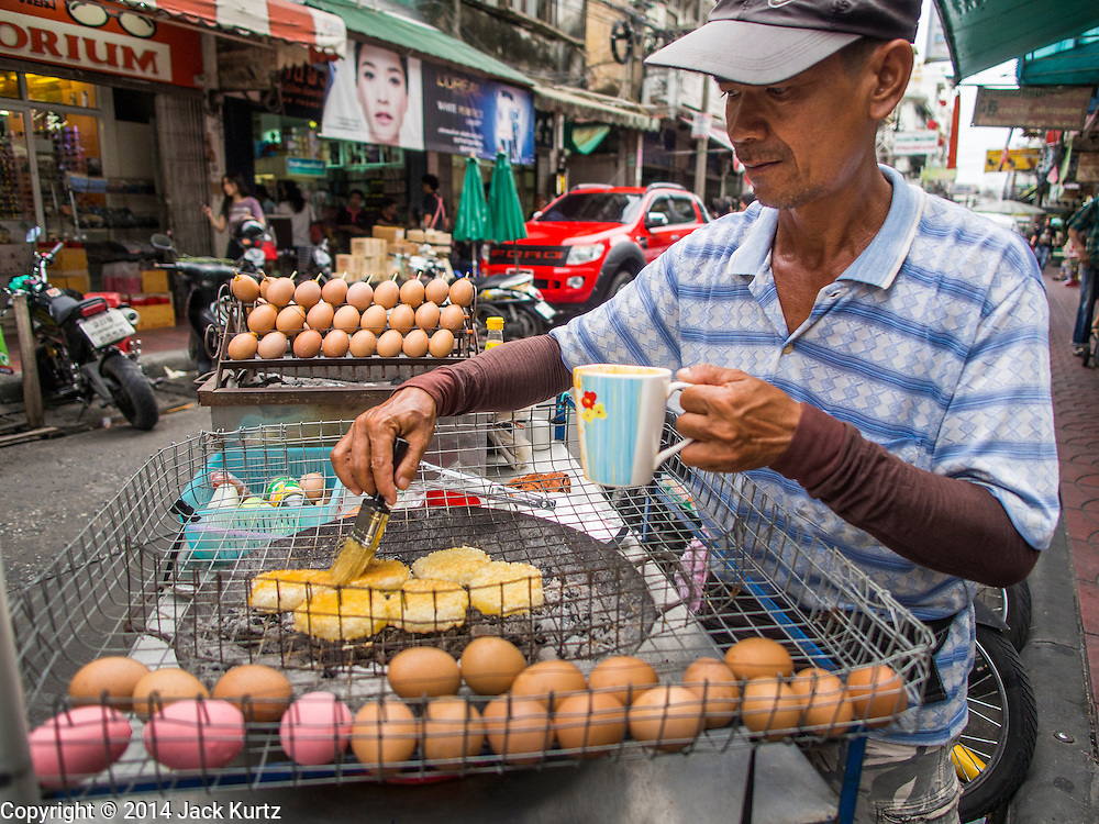 30 AUGUST 2014 - BANGKOK, THAILAND:  A street stall snack vendor prepares food in the Chinatown section of Bangkok.       PHOTO BY JACK KURTZ
