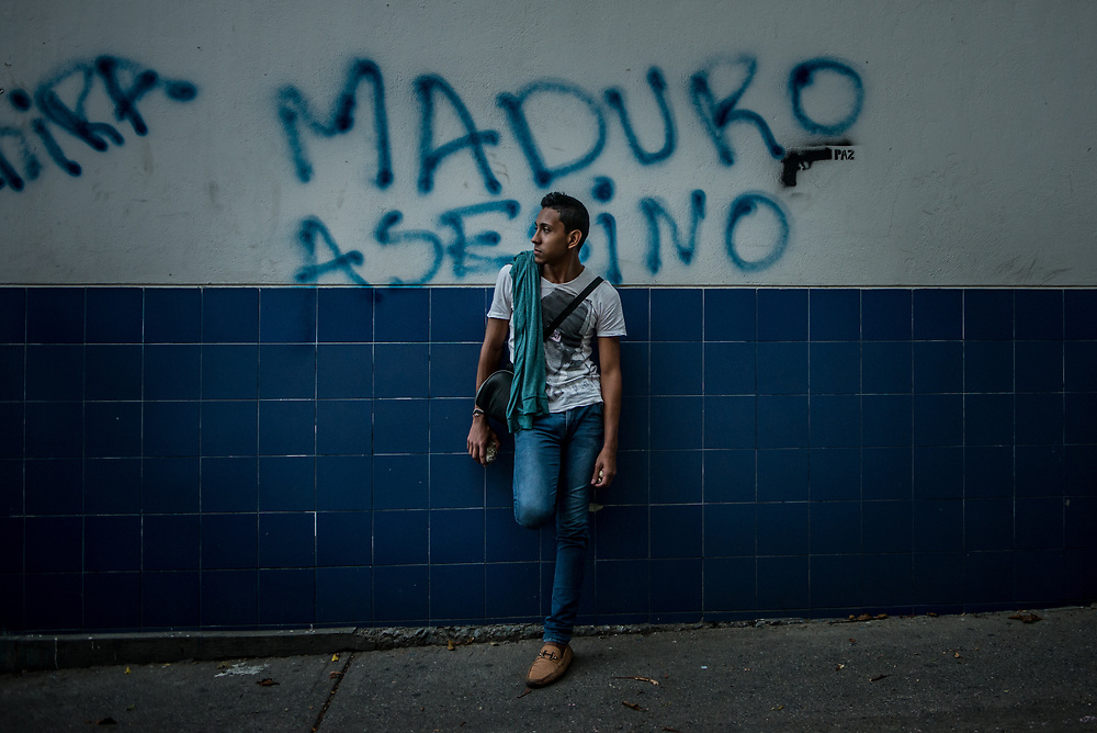 "CARACAS, VENEZUELA - MAY 22, 2017:  A man stands infront of street graffiti that says, ""Assassin Maduro"", referring to the Socialist President, Nicholas Maduro. Protesters are enraged at the government for becoming an increasingly repressive, authoritarian regime that has delayed elections, used armed government loyalist to threaten dissidents, called for the Constitution to be re-written to favor them, jailed and tortured protesters and members of the political opposition, and whose corruption and failed economic policy has caused the current economic crisis that has led to widespread food and medicine shortages across the country. The Socialist government refuses to take responsibility for causing the crisis and have instead vowed to fight back against those oppose them. ""If Venezuela was plunged into chaos and violence and the Bolivarian Revolution destroyed, we would go to combat,"" said President Nicholas Maduro. ""We would never give up, and what we failed to achieve with votes, we would do with weapons.""  PHOTO: Meridith Kohut"