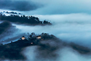 Houses of a small village located on a hill over the layer of clouds at sunrise