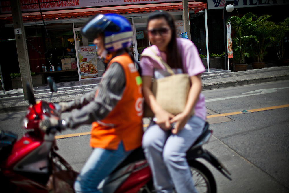 "Motorbike taxis are a common means of public transport in the urban chaos of Bangkok. Organized in groups, so called ""Win"", they reach out like the arms of an octopus from the main roads to bring their passengers deeper into the maze of smaller roads, the ""Soi"", where no other public transport (Skytrain or Buses) goes...While driving a motorbike taxi is usually a male domain, there is one group of motorbike taxis that is known as ""Win Pak Daeng"" or ""Win of the red lips"". More than 20 housewives, most of them married to soldiers work here together to earn some extra cash for the family household under an army license (their official jacket reads ""Army housewives"")...Despite occasional moments of discrimination or even harassment through male clients all of the women are very proud to be part of this group and enjoy the work. The great level of independence they have being their own boss is probably the major reason for them to brave the cities burning sun and tropical rains every day again. Being amongst friends is another one."