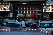 A young opera watcher stands outside a car before the start of Puccini's La bohème, performed by members of  English National Opera (ENO) as a drive-in (ENO Drive and Live) at Alexandra Palace, on 18th September 2020, in London, England. This is ENO's first public performance since the closure of their West End Colisseum home venue, because of the Coronavirus pandemic lockdown in March. This is Europe's first live drive-in opera production that audiences can safely experience from their cars and ENO's first public performance since the closure of their West End Colisseum home venue, because of the Coronavirus pandemic lockdown in March. As per the latest government advice. Each bubbled group consists of; 34 members of the<br /> ENO Orchestra, 20 ENO Chorus members and 8 principals. Each bubble has its own individual crew to oversee their rehearsals and performances.