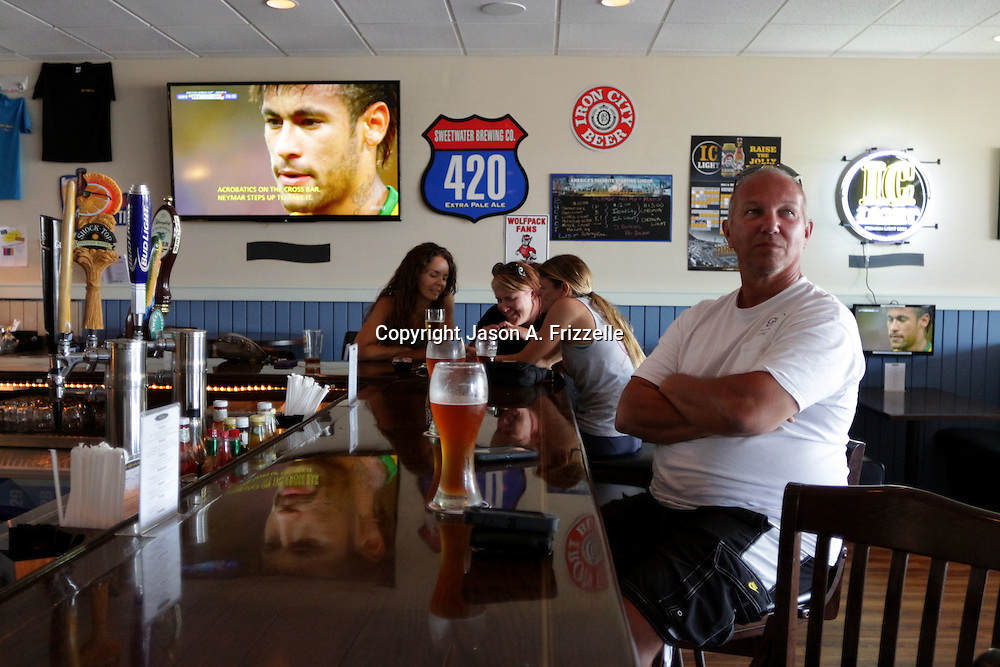 Patrons watch the opening match of the 2014 World Cup Thursday June 12, 2014 at Joe's Oasis in Wilmington, N.C. (Jason A. Frizzelle)