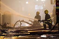 © Licensed to London News Pictures . 13/07/2013 . Manchester , UK . Two firemen with hoses work to quell the fire . A fire fighter is dead and two 15 year old girls are under arrest on suspicion of manslaughter after a blaze in Manchester yesterday (Saturday 13th July) . More than 60 fire fighters tackled a blaze at Paul's Hair World on Oldham Street in Manchester City Centre late in to the night (Saturday 13th July 2013) . Twelve crews from four stations were deployed . Several streets in a block in the city centre are sealed off . Photo credit : Joel Goodman/LNP