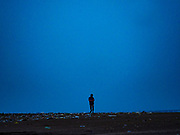29 JULY 2017 - AIRKUNING, BALI, INDONESIA:  A man walks on the beach in Airkuning, a Muslim fishing village on the southwest corner of Bali. Villagers said their regular catch of fish has been diminishing for several years, and that are some mornings that they come back to shore with having caught any fish.   PHOTO BY JACK KURTZ