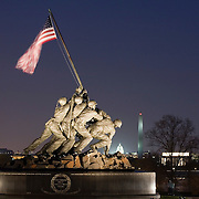 Iwo Jima Statue US Marine Corps Memorial Bronze sculpture by Felix DeWeldon near Arlington National Cemetary Arlington Virginia with the Washington Monument and the US Capitol Building in the background at night<br />