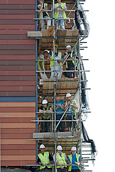© Licensed to London News Pictures. 25/07/2012. London, U.K..Builders stop work and on look from the scaffolding as The Olympic torch relay reaches Wembley Stadium today 25/7/2012, two days before the London Olympic 2012 games begin..Photo credit : Rich Bowen/LNP
