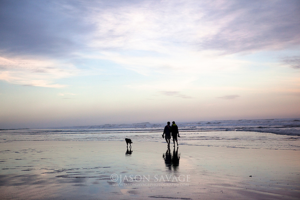 Couple walking on beach near Kalaloch. Olympic National Park, Washinton.