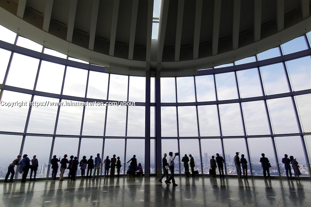 Visitors looking out over Tokyo from observation floor at Tokyo City View in Mori Building in Roppongi Tokyo Japan