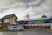 Car waits at railway crossing in Ascott-Under-Wychwood, Oxfordshire, United Kingdom