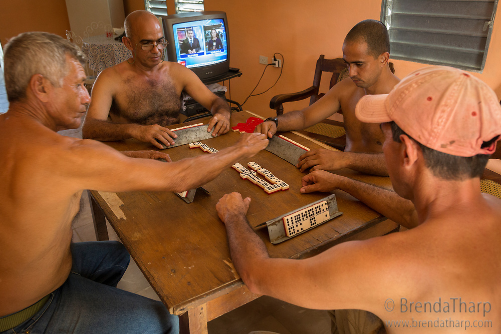 Cuba. Men gather to play dominoes inside a home in the town of Viñales, province of Pinar del Rio, while the TV broadcasts news.