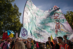 © Licensed to London News Pictures. 20/09/2019. London, UK. An activist waves a giant flag saying 'Amazonia' near Parliament as he takes part in the Global Climate Strike demonstration. Thousands of similar actions are taking place all over the UK and the rest of the world. Photo credit: Peter Macdiarmid/LNP