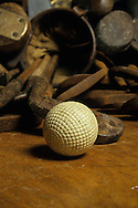 A ocobo molded gutta percha golf ball made in circa 1890, with old clubs in the background<br /> Picture Credit: Mark Newcombe