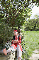 Young boy (7-9) wearing pirate costume sitting with crossed arms in garden