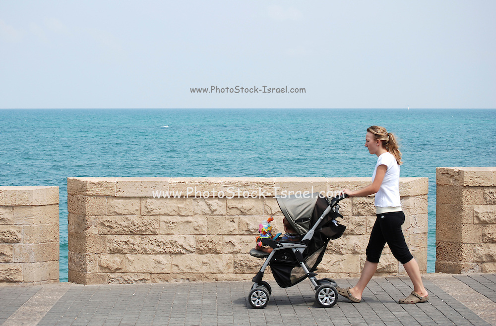 Israel, Tel Aviv-Jaffa, woman pushing a pram,  on the beach front promenade