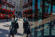 Londoners seen reflected in multiple plate glass windows on a busy summer lunchtime, in the Square Mile, the capital's historic financial district.