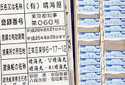 """Harumiya Co.'s business registration and employee time cards hang on the wall of the offices of the Yasuda family's """"yakata-bune"""" pleasure boat business in Tokyo, Japan on 30 August  2010. Photographer: Robert Gilhooly"""